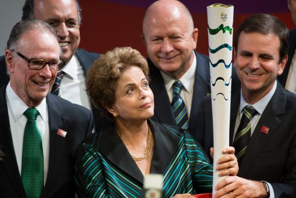 President Dilma Rousseff holding the Olympic torch, accompanied by the president of BOC Carlos Arthur Nuzman (left), and the Mayor of Rio de Janeiro, Eduardo Paes (right). Photo: Wikipedia.