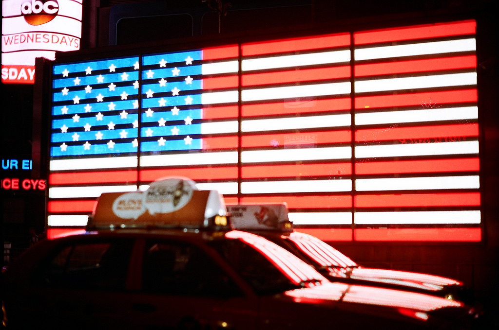Taxis drive past an illuminated American flag in New York Times Square. Photo: Harold Navarro/Flickr.