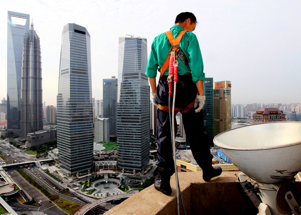 A migrant cleaner on the ledge of a high-rise building in Shanghai. (Photo / Xinhua via chinadaily.com)