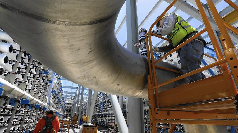 Steven Montes, right, installs a pressure relief valve on a 24-inch stainless steel pipe that will carry desalinated water from the thousands of reverse osmosis filters at the soon-to-be-opened desalination plant in Carlsbad, Calif. (Don Bartletti / Los Angeles Times). Image via latimes.com.