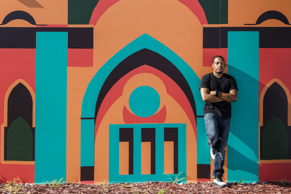 Architect/artist/city planner Germane Barnes in front of the Opa-Locka Community Development Corporations Arts & Recreation Center. Mural by Lekan Jeyifo. Photo: Matthew Roy, via Curbed.