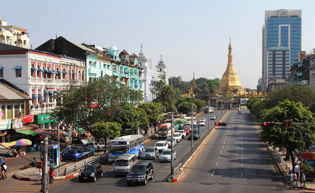 At the center of Yangon, the city's colonial heritage, Buddhist faith and emerging modern face are visible in a single block. (Frank Langfitt/NPR)