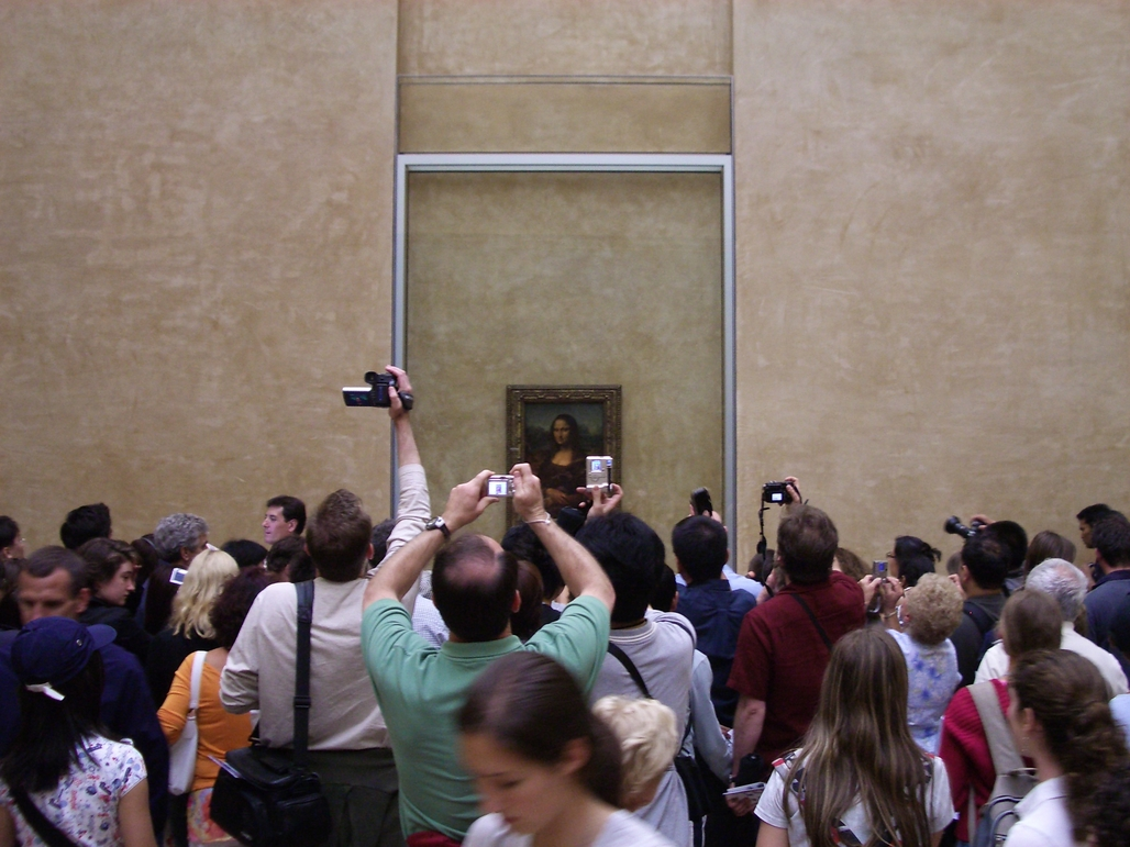 Visitors ogling perhaps the worlds most famous painting inside the worlds most famous museum. Credit: Wikipedia