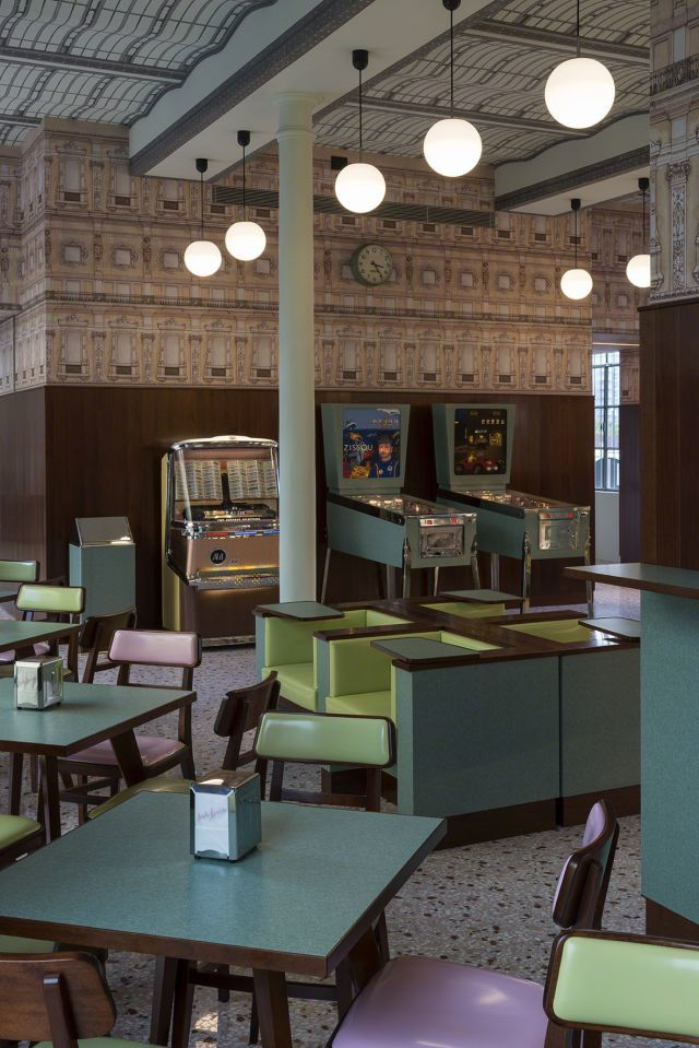 "Wes Andersons Bar Luce, which opens May 9 at the Prada Foundation Arts Complex in Milan, takes inspiration from a ""typical"" 1950 Milanese café. Yes, including a Steve Zissou pinball machine. (Photo: Fondazione Prada; Image via qz.com)"