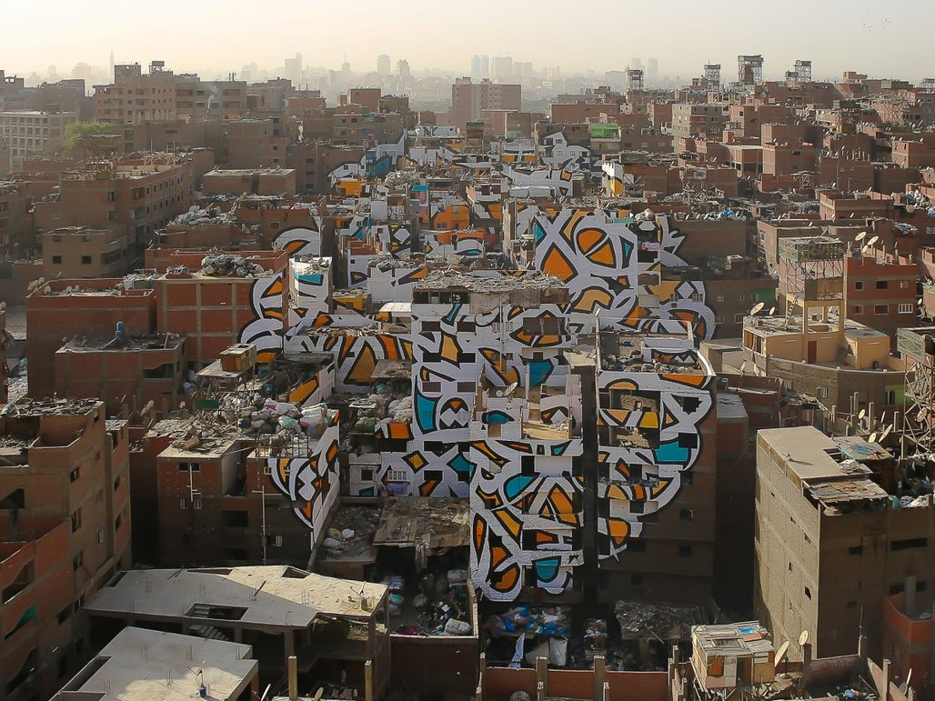 "The piece ""Perception"" by Tunisian-French artist eL Seed spans over numerous brick buildings in Cairos neglected Manshiyat Naser neighborhood. (Photo: eL Seed; Image via techinsider.io)"