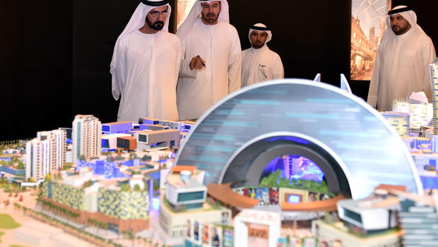 In this Saturday July 5, 2014, photo released by the Dubai Government Media Office, UAE Prime Minister and Dubai ruler Sheik Mohammed bin Rashid Al Maktoum, left, listens to Mohammed Abdullah Al Gergawi, center, chairman of Dubai Holding, during a presentation on the planned Mall of the World project. (CBS News; Photo: AP Photo/Dubai)