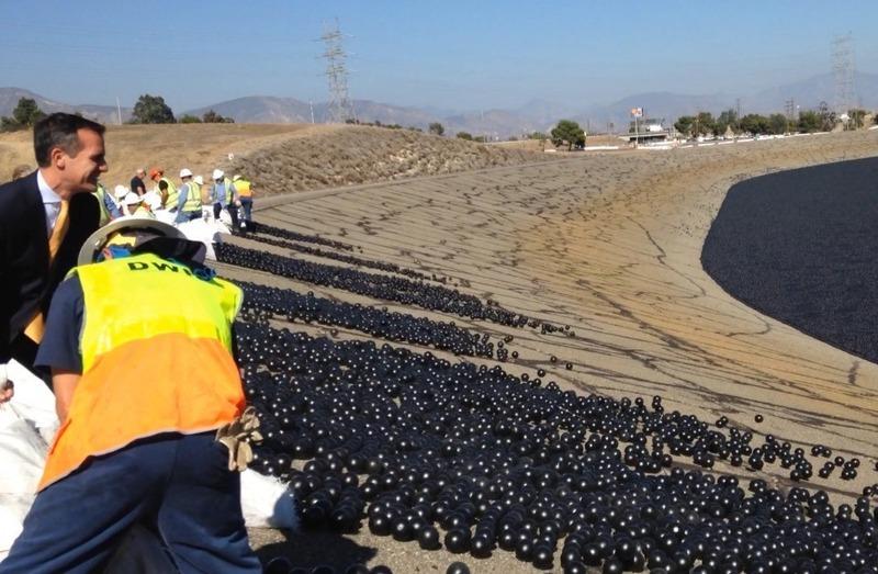 LA Mayor Eric Garcetti helps pitch 20,000 shade balls into the LA Reservoir. Image via atlasobscura.com