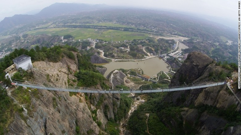 Originally made of wood, the bridge in Chinas Shiniuzhai National Geological Park has been converted to a glass walkway to attract a growing crowd of thrill seekers. (Image via cnn.com)