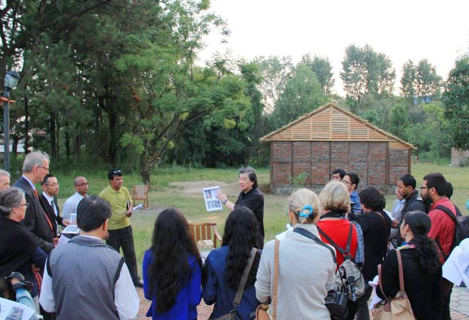 The photo shows Shigeru Ban presenting a Nepal House Project prototype in Kathmandu after the devastating 2015 Nepal earthquake. (Photo courtesy of VAN - Voluntary Architects Network)