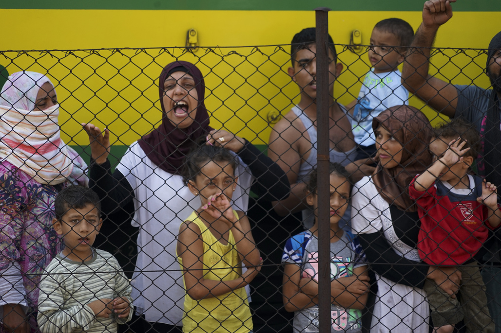 Women and children trying to escape from the conflict in Syria stand at a train station in Budapest. Credit: Wikipedia