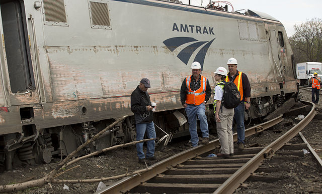 National Transportation Safety Board officials inspect the derailed Amtrak locomotive in Philadelphia. Photo via Wikipedia.