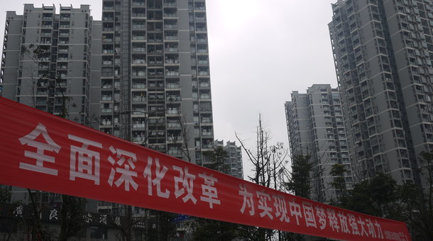 "A propaganda banner at an urban housing project for transplanted farmers in Chongqing reads: ""Deepen reform and unleash the power to realize the Chinese Dream"" The Southwestern Chinese city is attempting reforms to prepare for China's bold urbanization campaign, which aims to move 250 million farmers to the cities within the next 15 years. (Rob Schmitz/Marketplace)"
