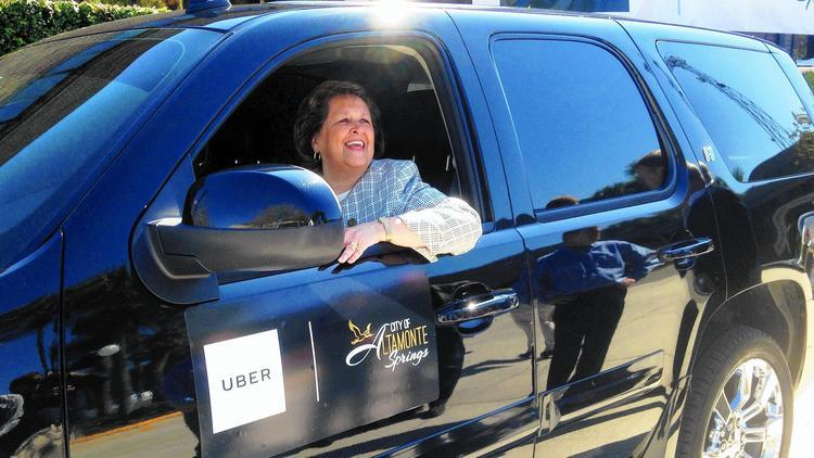 Altamonte Springs Mayor Patricia Bates sits at the wheel of an Uber vehicle at City Hall after announcing the new partnership between her city and the ride-sharing company on Friday. (Martin Comas, via Orlando Sentinel)