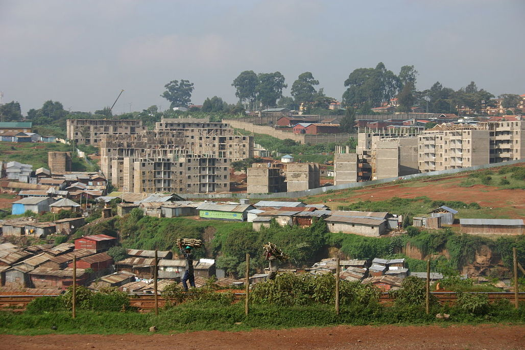 "The Kibera slums in Nairobi during the construction of the ""New Apartment"" project by the Kenyan Ministry of Housing and United Nations Habitat. According to leading experts, a universal basic income might prove more successful at poverty reduction than older models. Image via wikimedia.org"