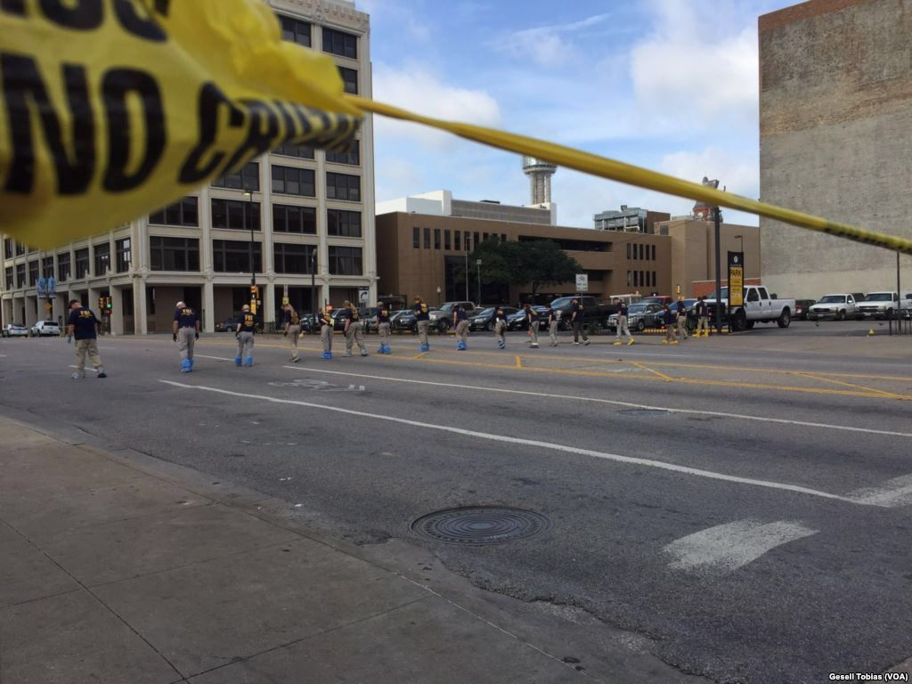 Law enforcement personnel investigate a mass shooting scene after a July 7 attack that killed and wounded Dallas police officers, in Dallas, Texas. Image via wikipedia.org.