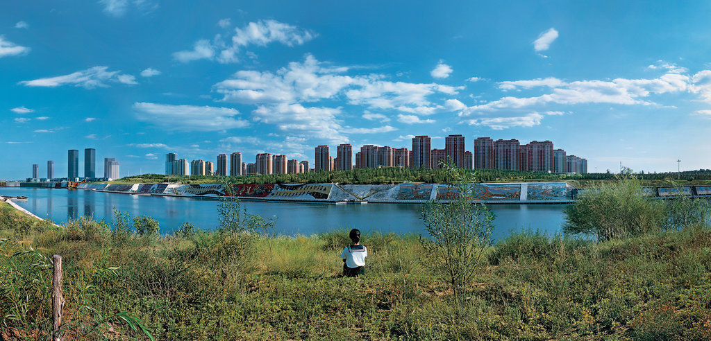 Two schoolgirls gazing out to Kangbashi New Area, formerly farmland and now the showpiece district of Ordos City, in China. Weng Fen