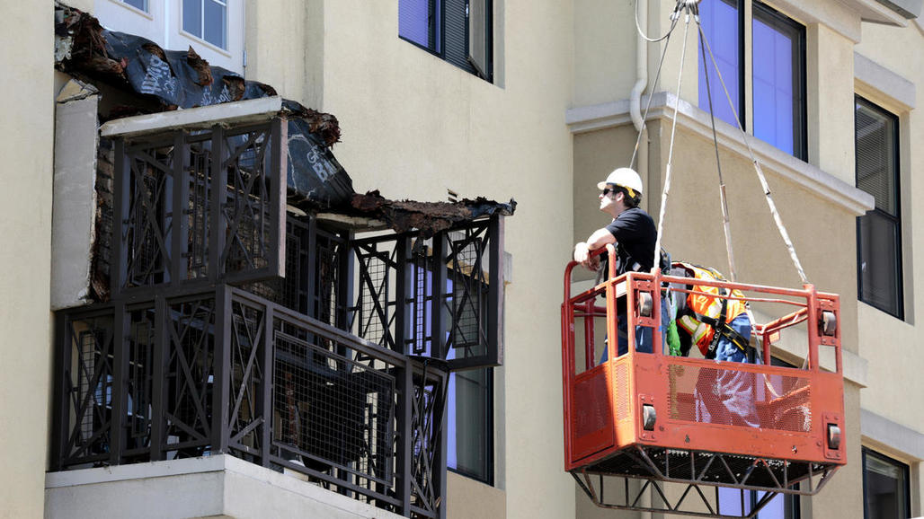 Engineers from Balfor Construction Co. examine what remains of a balcony at the 177-unit Library Gardens complex near UC Berkeley. Six people, all from Ireland, were killed when the balcony collapsed early in the morning. Image credit Mark Boster / LA Times.