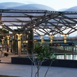 The canopy and reflective pool help integrate the Marina Bay Station into the park environment.