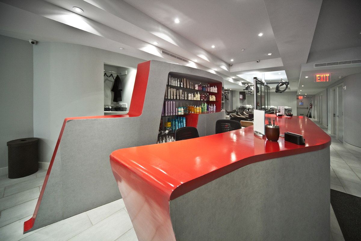 The curves of the reception desk, in Roy Teeluck red, integrates retail displays with the administrative and reception functions of a popular salon.