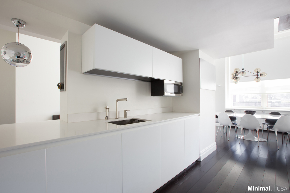 The design choice of the white countertop, not only lights up the small space, but also makes the kitchen sleek and clean while the upper cabinets complete the storage system with which the kitchen is equipped.