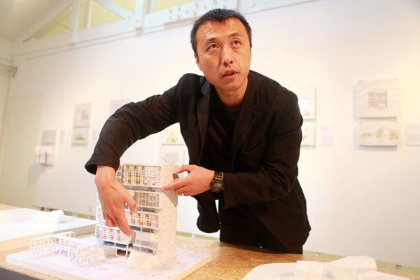 Li Hu displays a model of the Deep Ocean Research Base, one of Open Architectures projects, at Studio-X Beijing. Feng Yongbin / China Daily