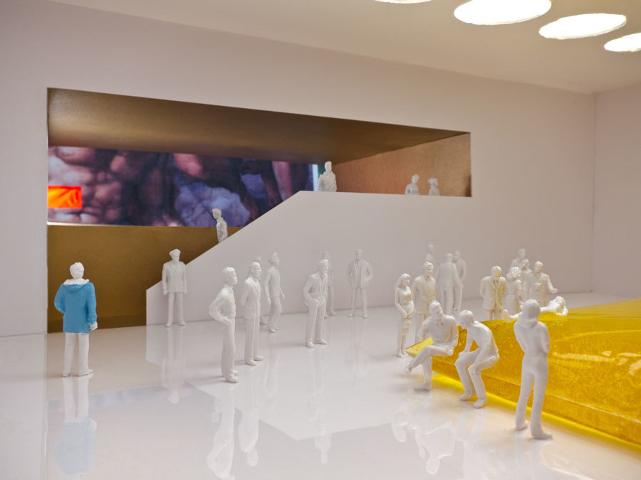 The Man in the Blue Coat walks through the gallery displaying a Gelatin special exhibit.