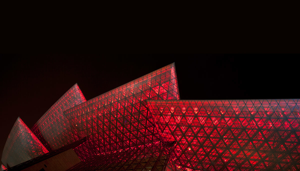At night time the perforated wing surfaces expose the space truss structures of the wings. The color of the LED lighting is changeable so that the building has a different appearance on different performance nights. (Photo: Jussi Tiainen)
