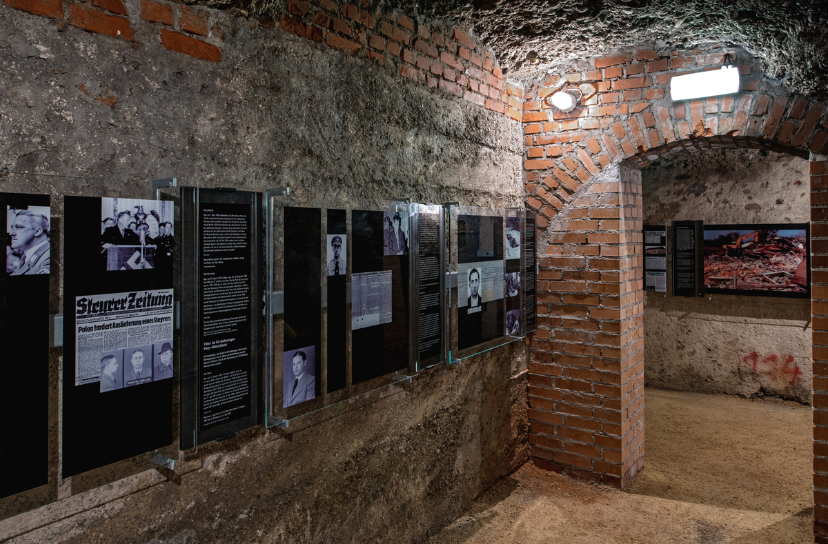 """Perpetrator Room: When entering the room, along with very minimalistic representations of the individual """"perpetrator profiles"""", a blow-up colour photo is visible outside the room. It shows the demolition of the last surviving barrack of the former Steyr-Münichholz concentration camp in 1993."""