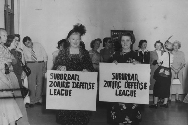 Two women hold signs which read, Suburban zoning defense league. February 16, 1957. Photo courtesy of The Los Angeles Public Library.