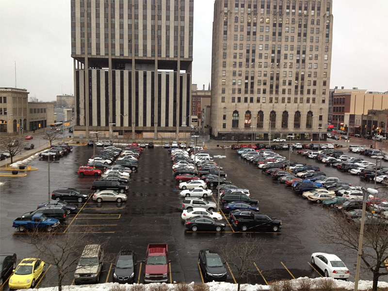 Current situation of Flints central downtown parking lot: Mott Foundation building is on the right; Genesee Towers, on the left, is slated for demolition (Image courtesy of Flat Lot Competition)