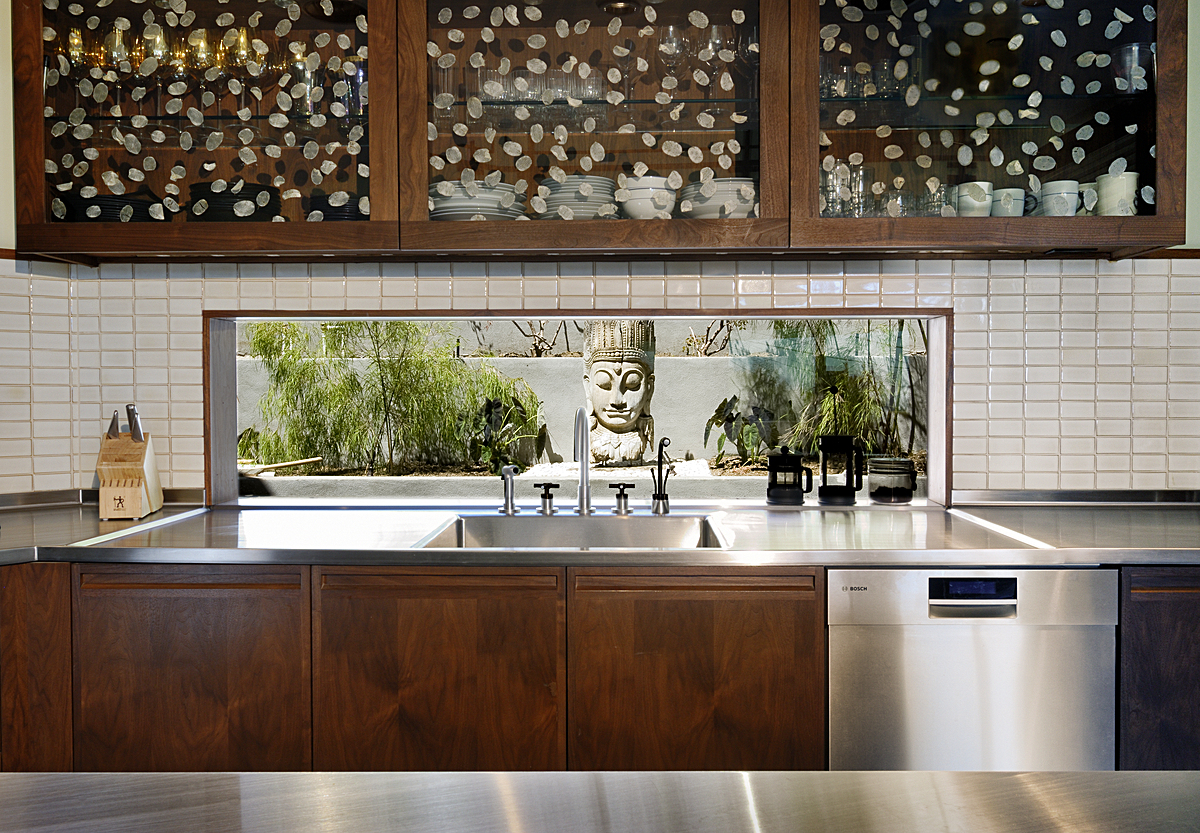A slot window was used instead of a traditional backsplash, opening the kitchen to the view of a small side yard. The cabinet fronts were inset with Livinglass, in which Roman Coin leaves were embedded in a resin layer between two sheets of recycled glass. White crackled tile from Ann Sacks.