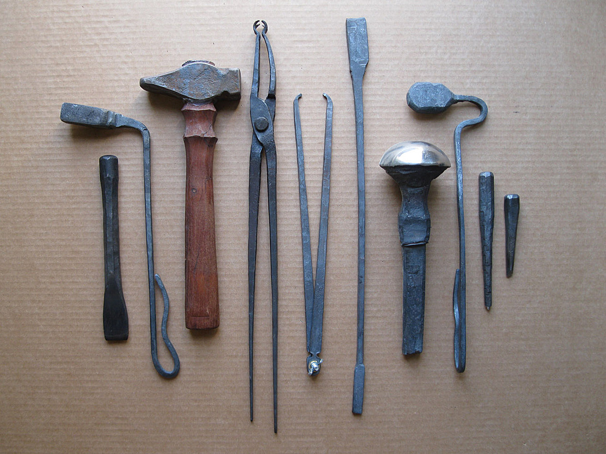 Tools made in William Bastas Toolmaking and Power Hammer classes. From Left to Right—chisel, fullering tool, hammer, tongs, caliper, hacker/snapper, mushroom stake, spoon shaped fullering tool, center punch, graver.