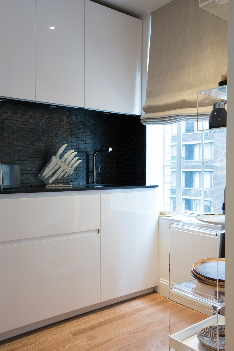 The black glass mosaic backsplash completes the elegance of the design creating silver reflections.