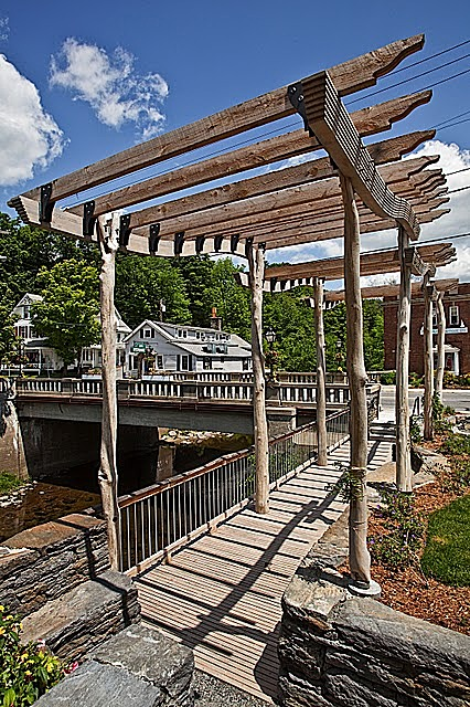 The Bank Park arbor and deck rest on the foundation of the Old Bank Building that burned down in 2003. The arbor structure gave new life to dead tree limbs found on the site. The new plants were grown at a local nursery and selected by resident Master Gardeners.