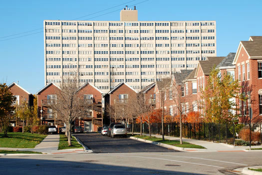 Old Town Village West townhomes, a new mixed-income development, ca. 2009; looming in the background is the William Green Homes high-rise, part of Cabrini-Green, demolished 2011. [Photo: Lawrence J. Vale]