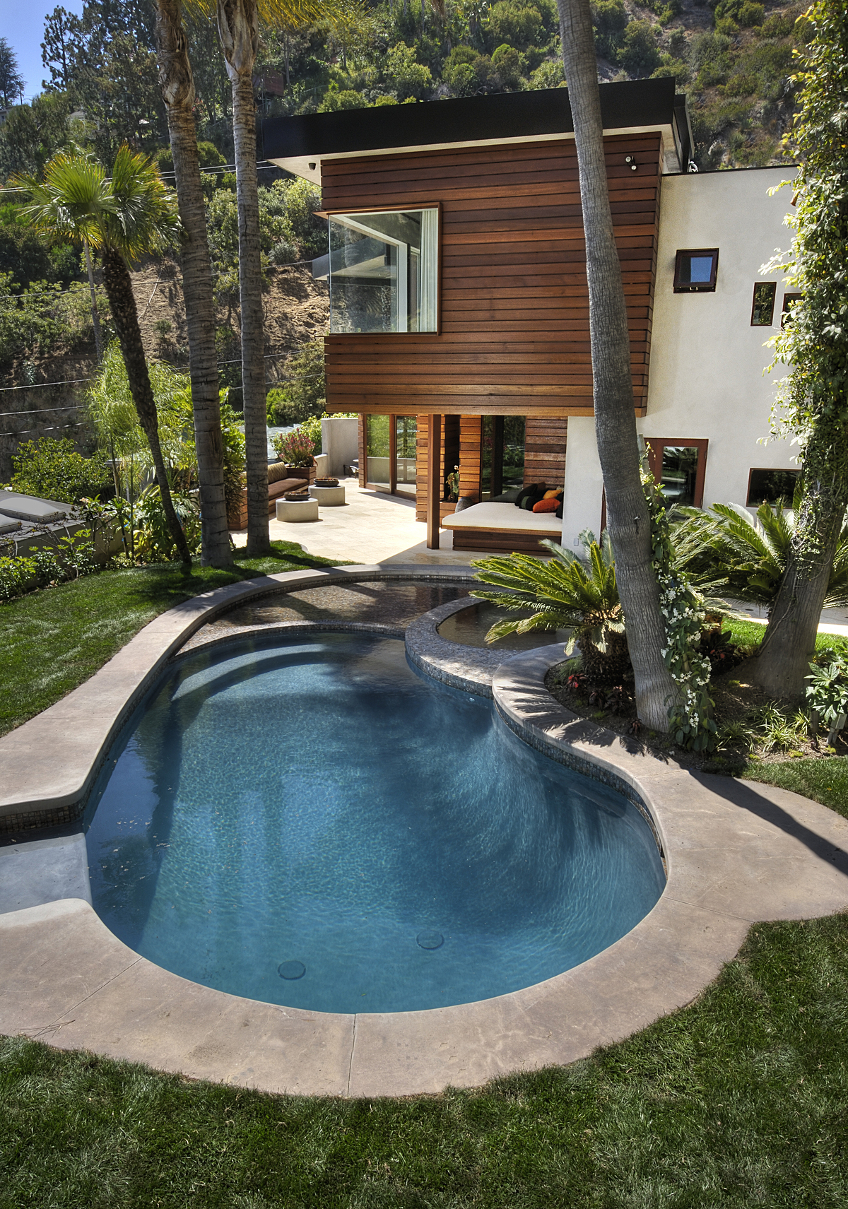 "Now shallower, the existing kidney shaped pool was redesigned to incorporate a jacuzzi and a 3"" deep wading pool for ""floating"" lounge furniture."