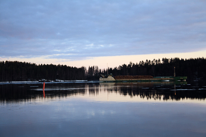 Logging boat gliding quietly through the lakes in Savonlinna, Finland.