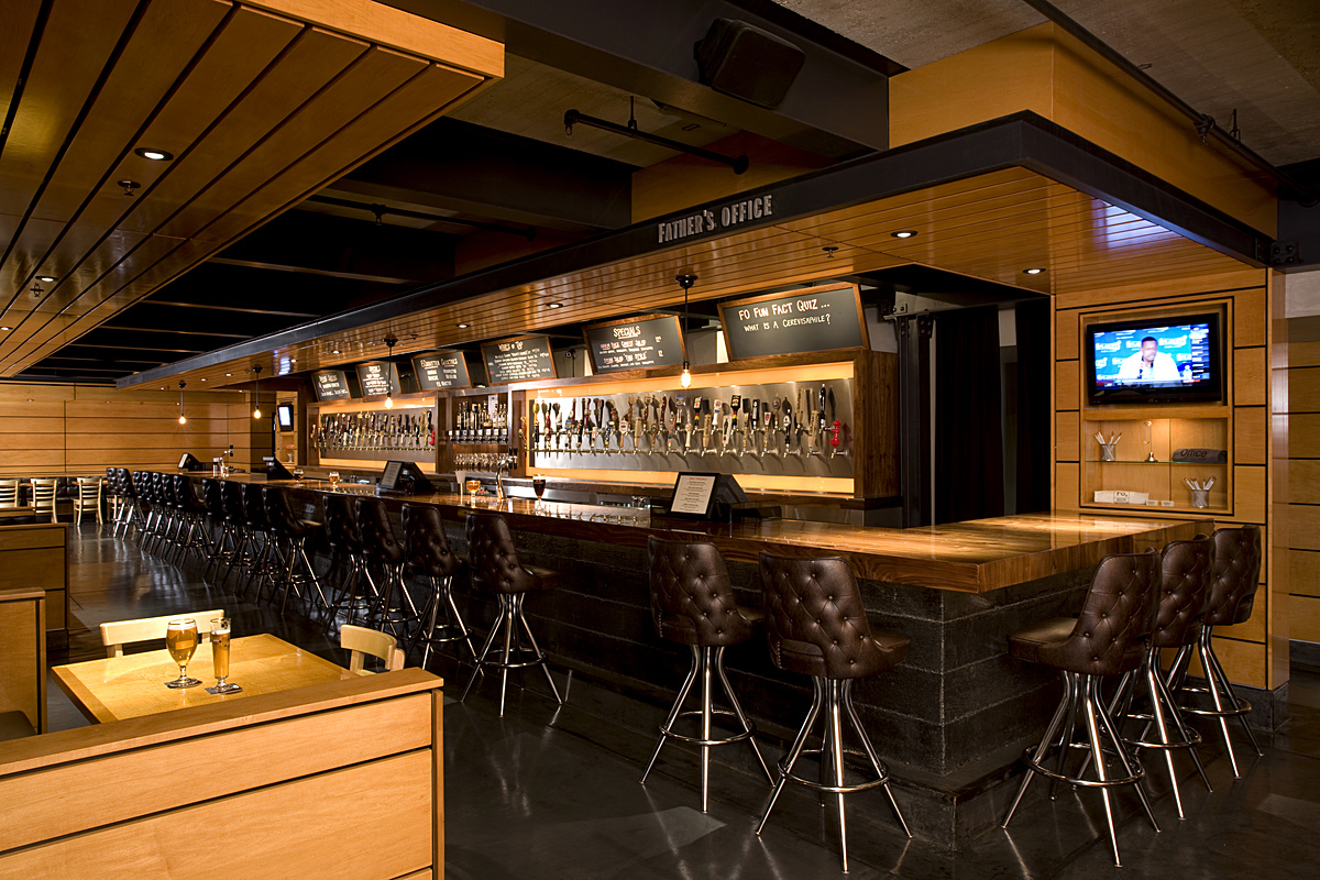 The back bar is a trophy wall that showcases each unique tap in its glory, and interior walls are then finished in wood panels in a luscious honey color with linear patterns to help create the effect of an elongated space.