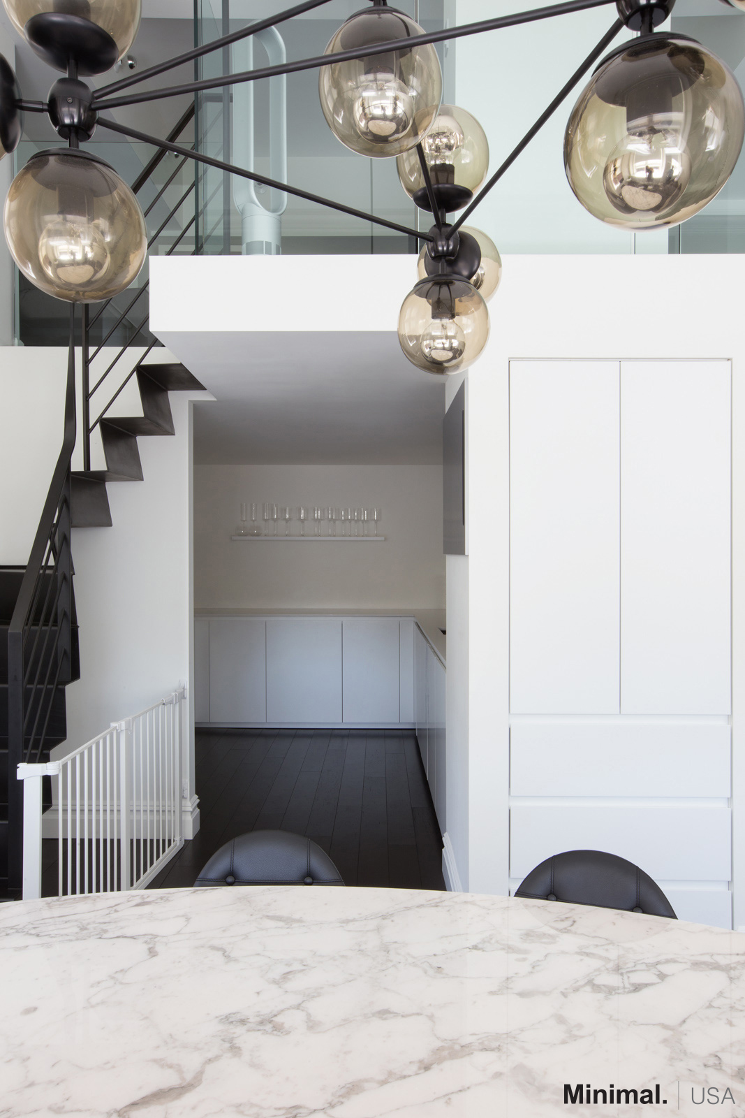 Moving to the left, passing the modern living room, there is the kitchens entrance with an adjacent pantry cleverly embedded in the wall, becoming an integral part of the column.