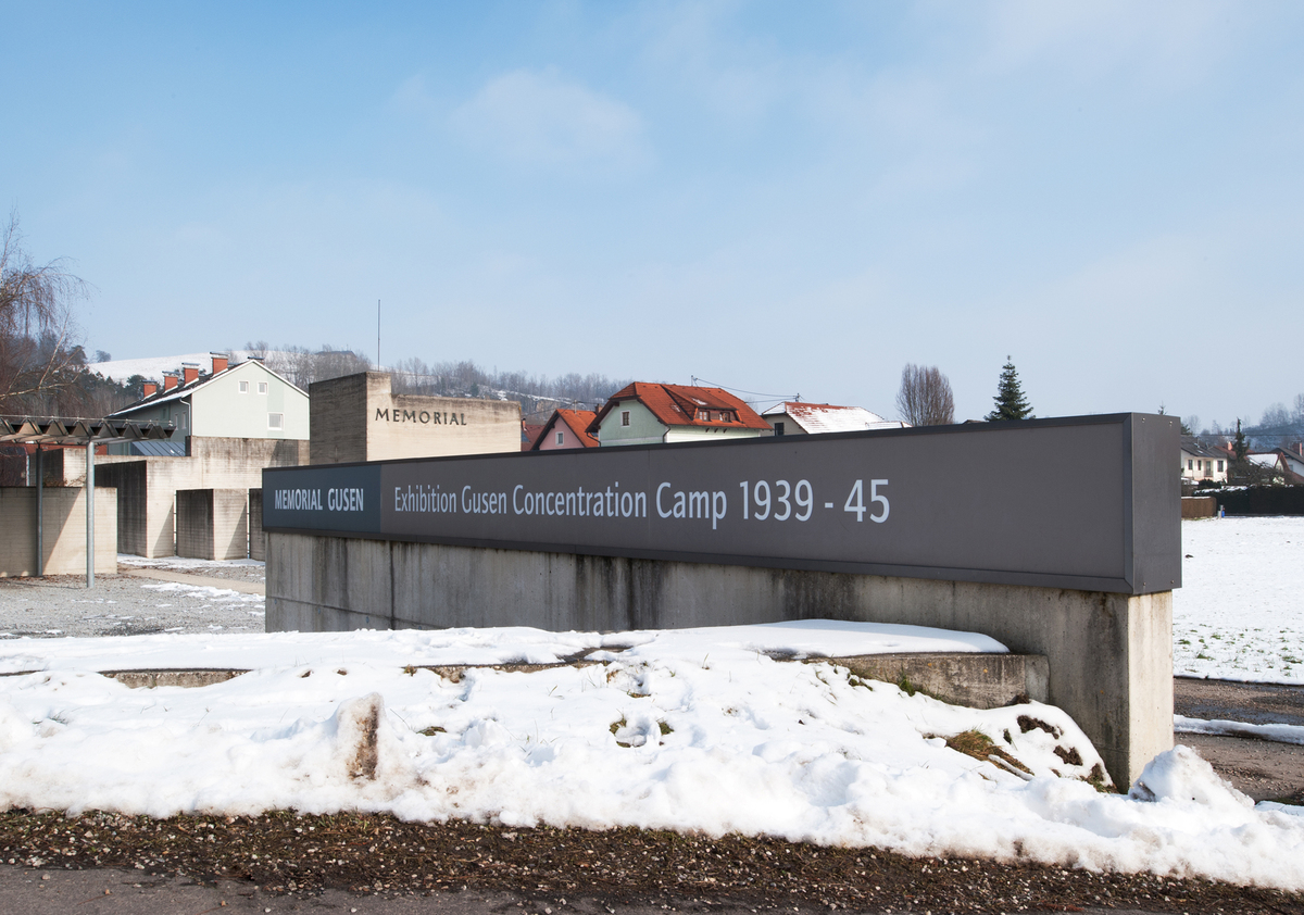Behind the sign can be seen the memorial of 1965. It is surrounded by residential buildings constructed in close vicinity to the memorial area.
