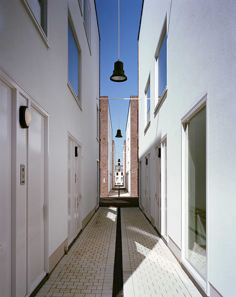 bright white alley facades with large windows and main entrances to the houses, ensure liveliness and interaction