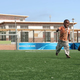 Young children running on the pitch of the Khayelitsha Football for Hope Center, the first completed Football for Hope Center. Location: Cape Town, South Africa. Credit: A. Grips