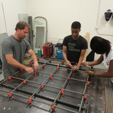 Studio H volunteer Eric Wandmacher and Studio H students Kerron Hayes and Alexia Williams construct a portion of the base for the Windsor Farmers Market pavilion. From IF YOU BUILD IT, a Long Shot Factory Release 2013.