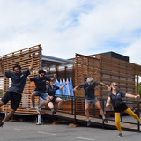 Team members from California Polytechnic State University, San Luis Obispo, kick up their heels during a team cheer at the U.S. Department of Energy Solar Decathlon at the Orange County Great Park, Irvine, California, Monday, Oct. 12, 2015. (Credit: Richard King/U.S. Department of Energy Solar...