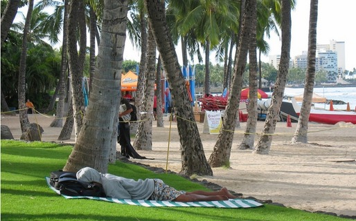 A homeless individual sleeps on the beach in Waikiki. Credit: Cathy Bussewitz / AP Images