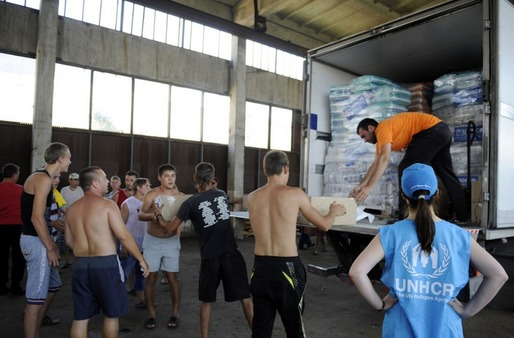 Refugees in E. Ukraine unload supplies provided by the UN. Via: Al Jazeera, Alexander Khudoteply/AFP/Getty Images