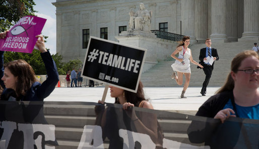 Television network producers ran past demonstrators outside of the Supreme Court on Thursday. Credit: Stephen Crowley, image via nytimes.com