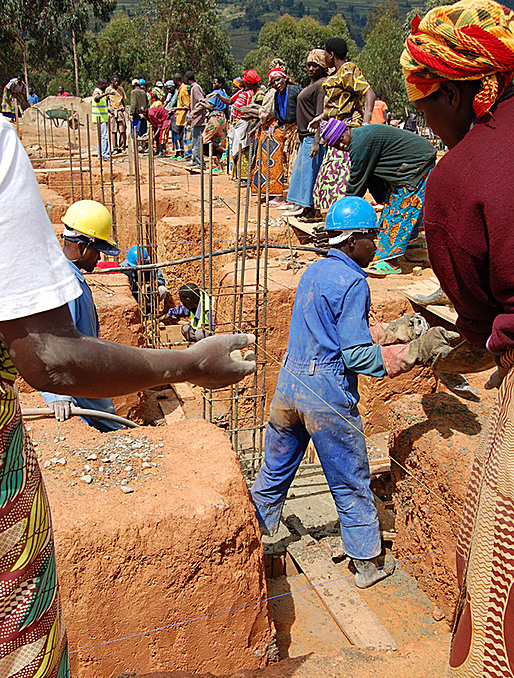 Community members pour concrete for foundations. (Photo courtesy of MASS Design Group)