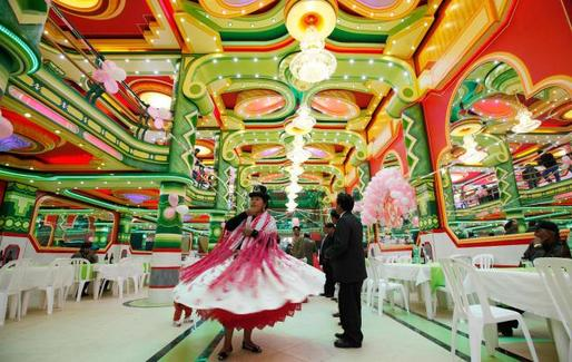 In this May 17, 2014 photo, an Aymara woman dances in a ballroom of one of the newfangled mini-mansions rising up in El Alto, Bolivia. (USNews; AP Photo/Juan Karita)