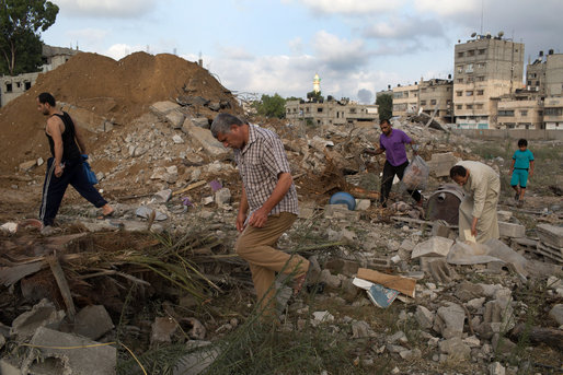 Palestinian men search for bodies among the ruins of a building. Credit: Tyler Hicks / NY Times